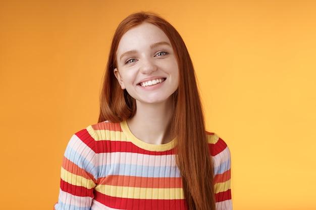 친절 한 여성 예쁜 빨간 머리 백인 여성 형제는 광범위 하 게 웃 고 완벽 하 게 행복 한 분위기를 부담없이 편안 하 게 기쁘게 서 오렌지 배경 서 좋은 여름 화창한 날을 즐길 수 있습니다.