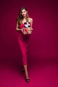 광고 복사 공간 핑크 스튜디오 배경에 포즈 축제 이브닝 드레스를 입고 선물을 가진 친절 맞는 젊은 여자