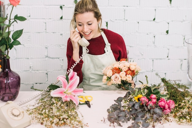 Дружелюбный флорист, разговаривающий по телефону