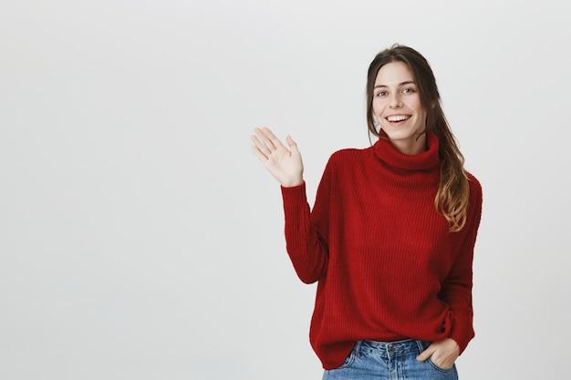 Дружелюбная девушка в свитере машет рукой, поздоровайся
