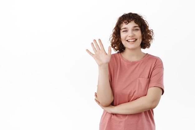 手を振って笑って、挨拶して、こんにちはと言って、白の上に立って、こんにちはジェスチャーで誰かを歓迎するフレンドリーな女子学生