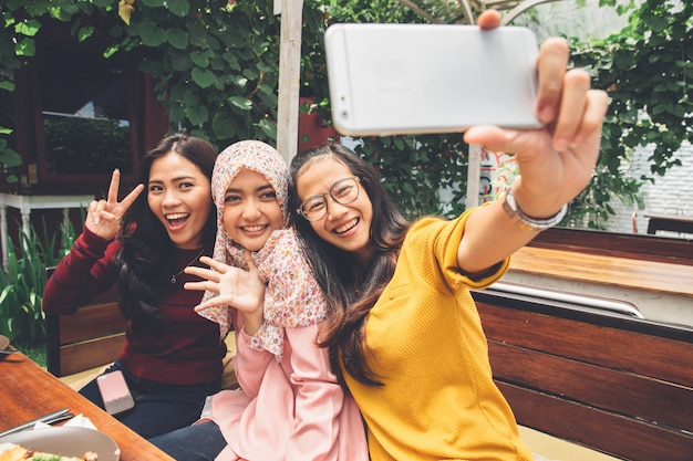 Friendly girls making selfie in cafe