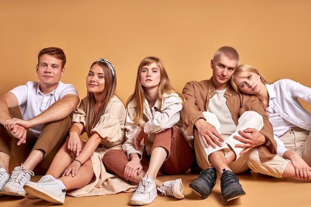 スタジオの床にいる学生の若者のフレンドリーなグループ