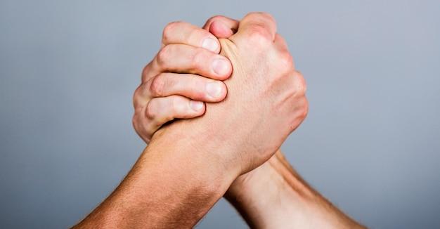 친절한 악수, 친구 인사, 팀워크, 우정. 악수, 팔, 우정. 손, 경쟁, 대, 도전, 힘 비교. 남자 손. 두 남자 팔 씨름.