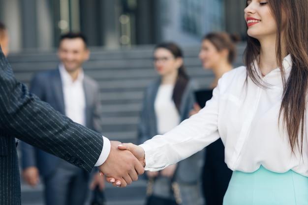 フレンドリーな握手男と女。屋外の2つのビジネス人々の会議。認識できないカップルお互いに挨拶します。多文化の握手手クローズアップショット。