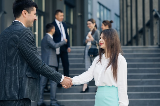 Friendly handshake man and woman. meeting of two business people outdoors. persons greeting each other. businessmen shaking hands.