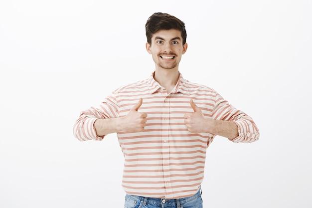 Amichevole bel ragazzo adulto in camicia a righe, mostrando il pollice in alto e sorridendo felicemente, apprezzando l'idea e dando approvazione, esprimendo un atteggiamento positivo