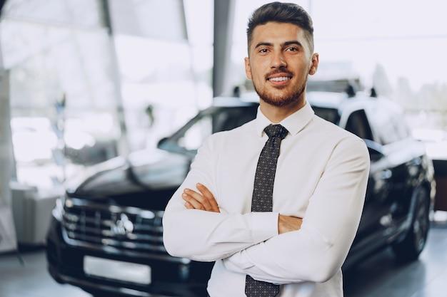 車のサロンに立っているフレンドリーなハンサムな車売り手男