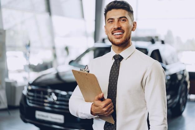 자동차 살롱에 서 친절 잘 생긴 자동차 판매자 남자
