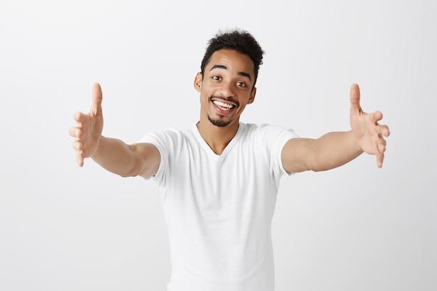Friendly handsome dark-skinned guy reaching hands, holding something, embracing or giving hug