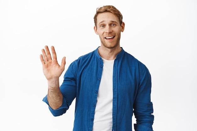 빨간 머리를 한 친근한 잘 생긴 남자가 인사하고, 손을 흔들며 웃고, 인사하며 친구에게 인사하고, 흰 벽 위에 서 있습니다.