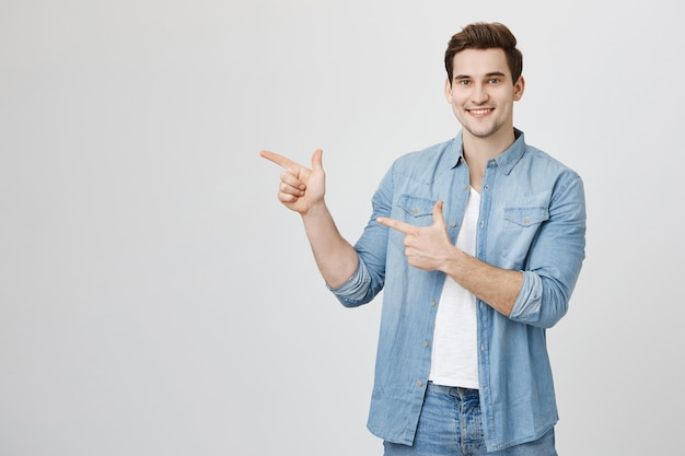 Friendly handsome man pointing fingers left at advertisement