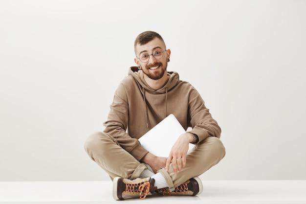 Uomo bello amichevole si siede sul pavimento con il computer portatile e sorridente