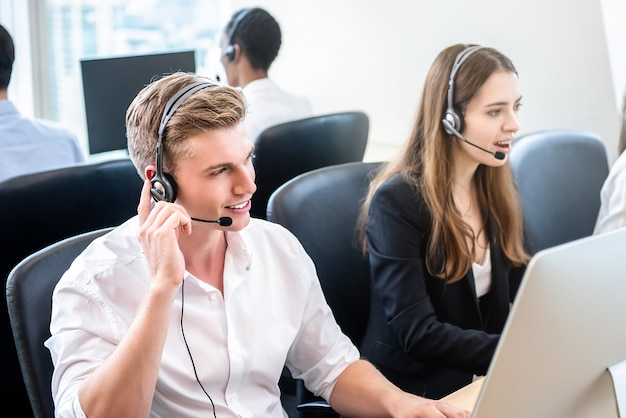 Friendly handsome man working in call center office with team