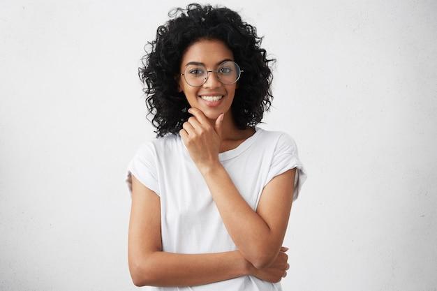 カジュアルなtシャツと大きな丸い眼鏡をかけているフレンドリーな幸せなアフリカ系アメリカ人のティーンエイジャー