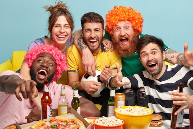 친절하고 행복한 네 명의 젊은 남자와 한 여자가 tv 화면을 포용하고 즐겁게 바라보고, 텔레비전과 재미있는 영화를보고, 축구 공을 들고, 집에서 즐거운 시간을 보냅니다.