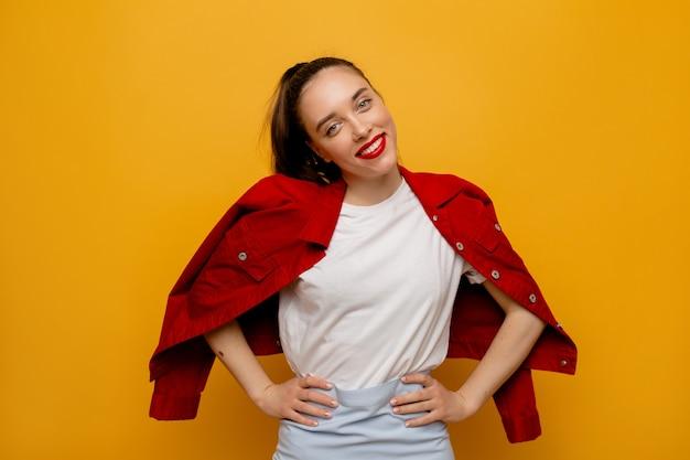Amichevole ragazza felice che indossa maglietta bianca e giacca rossa sorridente e in posa su giallo