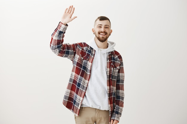 Friendly happy hipster guy waving raised hand to say hello, greeting you