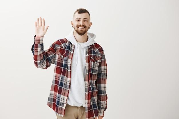 Ragazzo amichevole hipster felice agitando la mano alzata per dire ciao, salutandoti