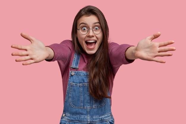 Дружелюбная счастливая радостная женщина обнимает, одетая в джинсовый комбинезон и фиолетовый джемпер, смотрит от счастья