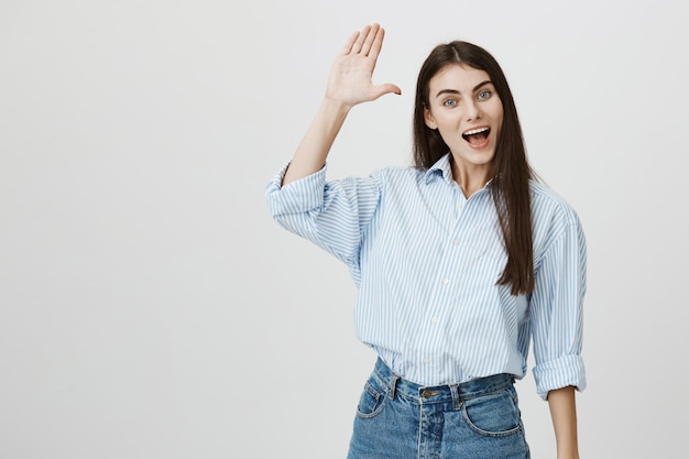 こんにちは、ジェスチャーの挨拶で手を振ってフレンドリーな幸せなきれいな女性