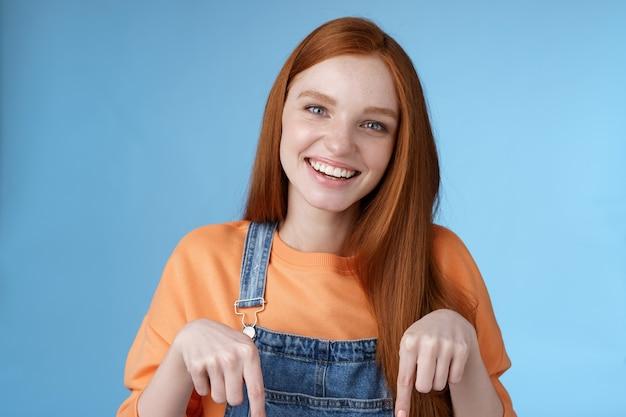 Amichevole ragazza rossa felice sorridente vivace bel sorriso rivolto verso il basso dita indice offrendo una buona offerta consiglia di utilizzare il servizio in piedi sfondo blu discutere di un prodotto interessante, sfondo blu