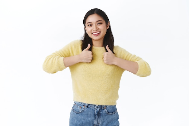 Friendly happy young asian woman showing thumbs-up and smiling, giving positive reply, approve idea, like awesome event, recommend check out cool offer at store, standing white wall