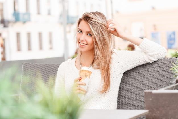 세련된 빈티지 스웨터에 귀여운 미소로 친절한 행복 한 젊은 여성이 앉아서 거리 카페에서 경적에 달콤한 아이스크림을 먹는다. 아름다운 명랑 소녀는 주말을 즐깁니다.