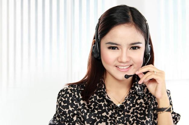 コールセンターのオペレーターの電話を笑顔のフレンドリーなヘルプデスク女性
