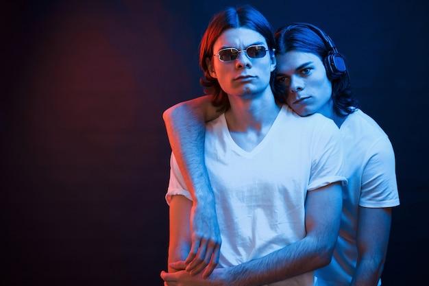 Дружеское объятие. портрет братьев-близнецов. студия снята в темной студии с неоновым светом.