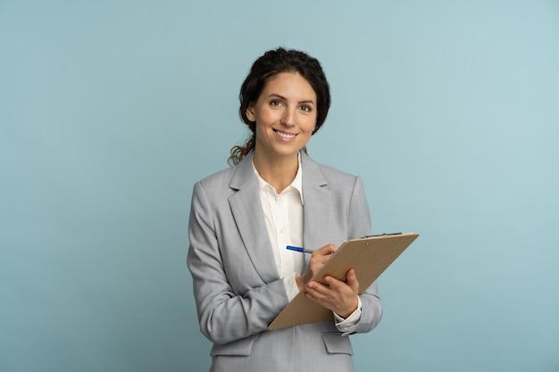 Дружелюбный инструктор или женщина-агент в сером пиджаке с папкой, ручка смотрит в камеру