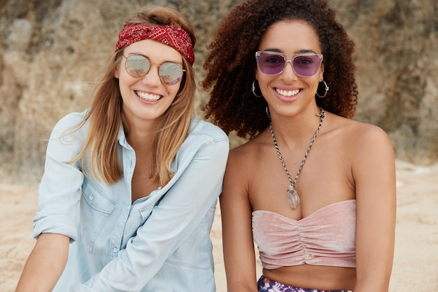 Friendly interracial women wear trendy sunglasses and summer clothing, being in high spirit as breath fresh marine air, have happy expressions, sit on sandy beach.