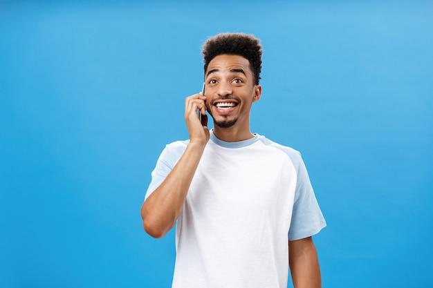 Приветливый, веселый, беззаботный темнокожий парень с бородой в повседневной футболке радостно болтает о забавных футболках ...