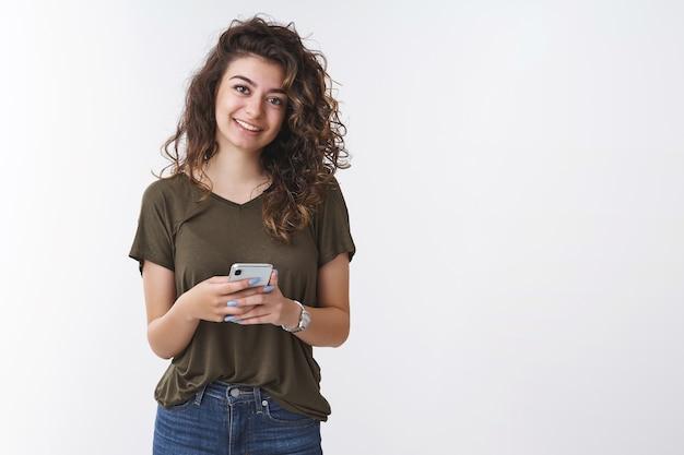 フレンドリーで楽しい若い女性が新しいスマートフォンアプリをテストして元気に笑ってカメラを見て喜んでポストインターネットブログ、立っている白い背景、新しい財布のオンラインストアを選んでください