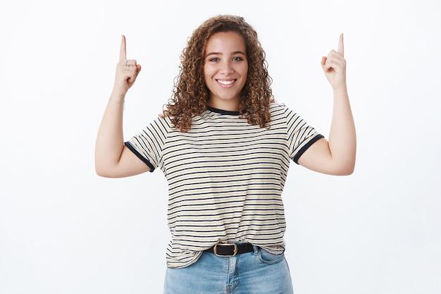 フレンドリーで活気に満ちた魅力的な若い女性の白い歯は、人差し指を上に向けて方向を示し、クールなプロモーションの戦いの不安を促進し、自尊心を上向きに持ち上げます