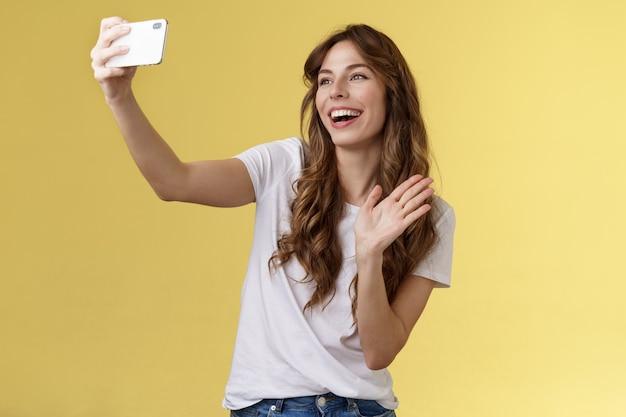 フレンドリーで活気のある格好良い陽気なフェミニンな女の子が腕を伸ばすスマートフォンの記録ビデオブログwavi ...