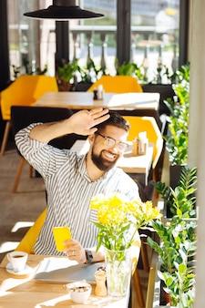 친절한 표정. 그의 친구에게 손을 흔드는 동안 창을 들여다보고 기쁘게 긍정적 인 남자
