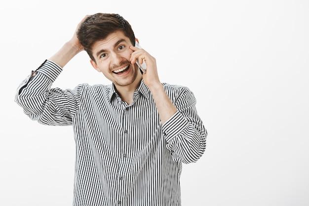 Studente maschio europeo attraente dall'aspetto amichevole con barba e baffi, grattandosi la testa e sorridendo ampiamente mentre parla sullo smartphone, dimenticando qualcosa e sentendosi a disagio nel chiedere favore
