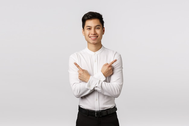 Friendly-looking attractive successful asian male entrepreneur give advice where find everything need, pointing sideways, make cross over body and point left and right,