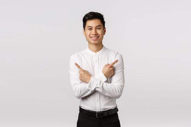 Доброжелательно выглядящий привлекательный успешный азиатский предприниматель мужского пола дает советы, где найти все необходимое, указывая в сторону, пересекает тело и указывает влево и вправо,
