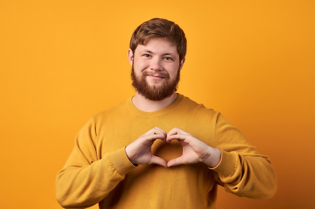Приветливый бородатый парень формирует сердечный жест, передает любовь, благотворительность и волонтерство