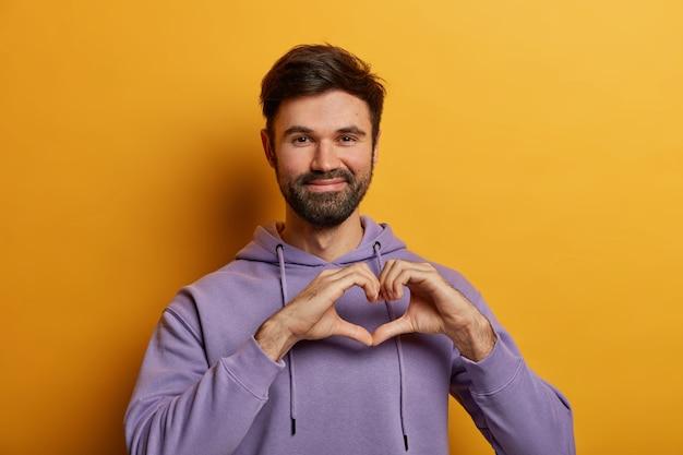Ragazzo barbuto dall'aspetto amichevole modella il gesto del cuore, invia amore, beneficenza e volontariato, indossa una felpa viola, posa sul muro giallo, dimostra affetto