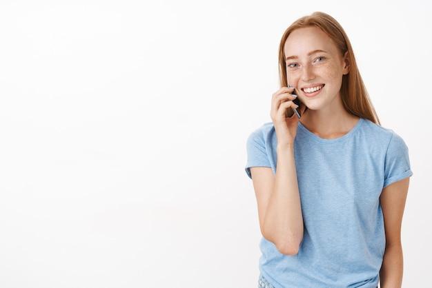 赤い髪とそばかすのあるフレンドリーな魅力的な社交的な女性が携帯電話を耳の近くに保持しているスマートフォンで話している間、電話は笑顔で面白がって、灰色の壁の上でリラックス