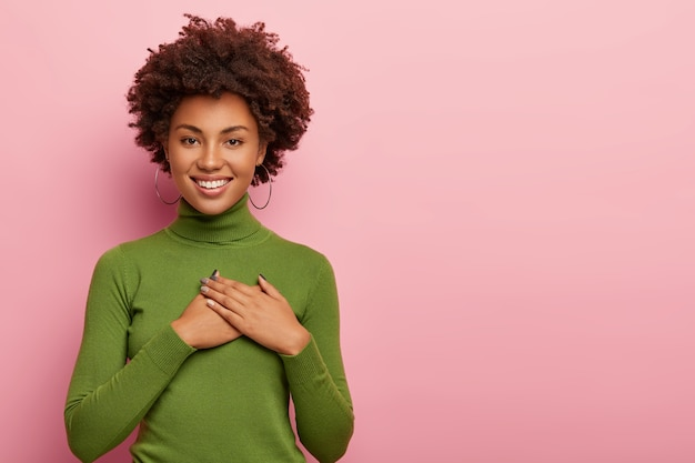 Friendly looking dark skinned woman feels thankful, expresses gratitude, has heart filled with love, keeps both palms on chest, wears green turtleneck, poses over pink background, copy space