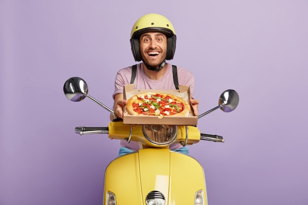 Friendly looking deliveryman driving yellow scooter while holding pizza box