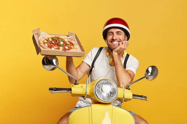 Friendly looking deliveryman with helmet driving yellow scooter while holding pizza box