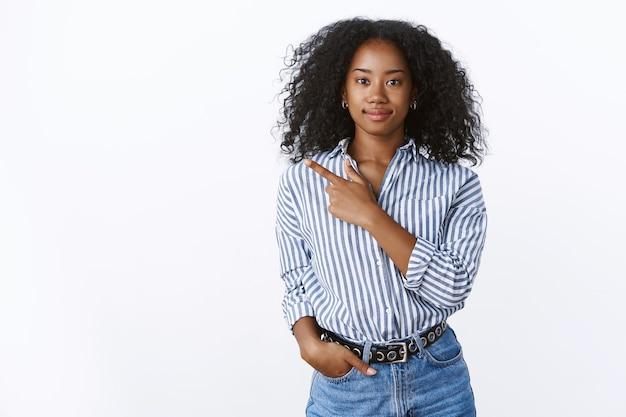 친절하게 보이는 쾌활한 젊은 아프리카계 미국인 여성 고객은 집게손가락이 웃고 있음을 나타내는 흰색 벽을 옆으로 가리키는 포즈를 취하고 있습니다.
