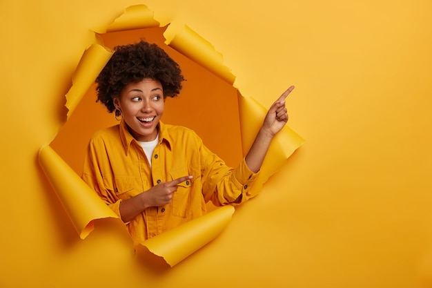 Friendly looking ethnic woman recommends blank space for your advertising content, stands pleased in paper hole wall, smiles happily