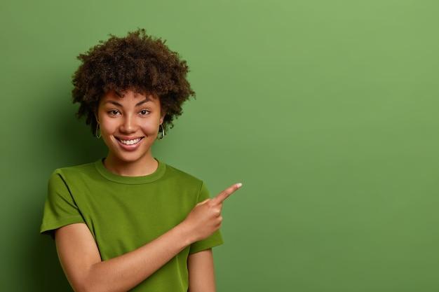 친절하고 기쁜 여성 상점 조수가 고객을 돕고, 상점에서 할인을 보여주고, 녹색 벽 위에 빈 공간에 앞쪽 손가락을 옆으로 가리 킵니다.