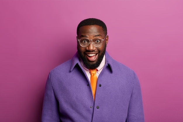 Friendly looking glad man laughs at camera, has funny conversation with interlocutor, wears transparent glasses, bright purple jacket, has toothy smile